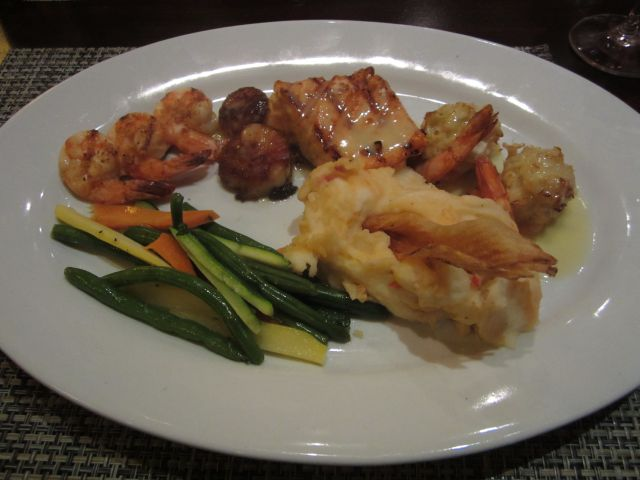 Ultimate Seafood Platter with Shrimp, Scallops, Salmon. Served with Mash Potatoes and Vegetables.