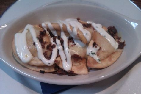 Fried Potato and Cheese Pierogies with Onion and Applewood Bacon Bits topped with Melted Havarti Cheese and Herb Sour Cream