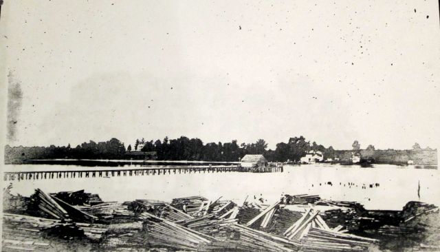 Showing Port Royal Wharf and Lumber Ready for loading opposite Port Conway. If you look to the left on the high bank you will see Belle Grove. Across the river is Port Conway's Ferry and Wharf. Today this area is lost to the wooden area around Belle Grove and the James Madison Bridge.1906